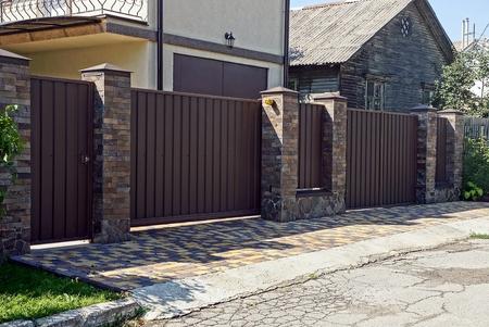 Gray brown iron fence in front of asphalt road Standard-Bild