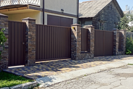Gray brown iron fence in front of asphalt road Фото со стока