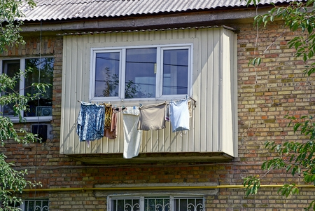Clothing and laundry dries after washing the balcony on the wall of the house