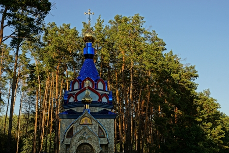 street creed: Colored christian church in nature in a pine forest