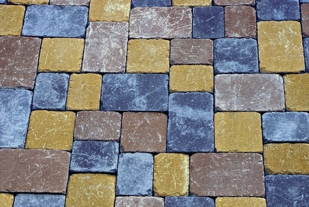 Colored texture of a fragment of paving bricks on the road