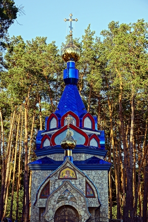 street creed: Beautiful colored Christian temple in a pine forest Stock Photo