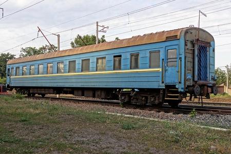 dirty: Blue passenger car on rails on the railway