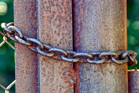 communications tools: Brown rusty iron pipe and steel chain on the fence