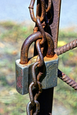 Old and rusty padlock with chain on the fence