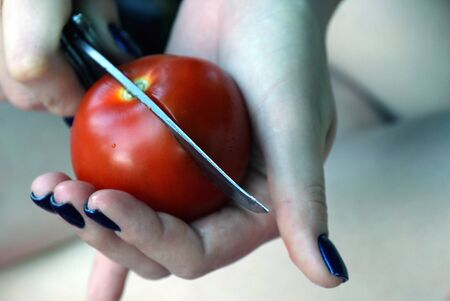 Red tomato in the hands of a girl cut with a knife