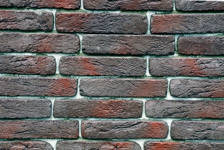 Colored texture of dark bricks on the wall of the house