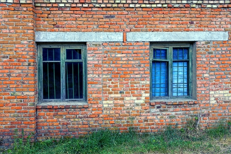 Two old windows behind a lattice on a brick wall Stock Photo