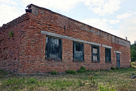 Old brown brick house with broken windows in the grass Stock Photo