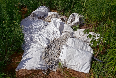 Bags with construction debris on a pile in green grass Stock Photo