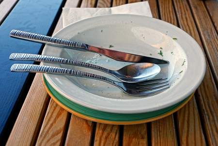 residue: Dirty dishes with cutlery on a brown wooden table Stock Photo