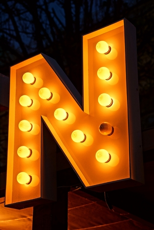 publicidad exterior: Big letter on advertising in glowing bulbs in the dark