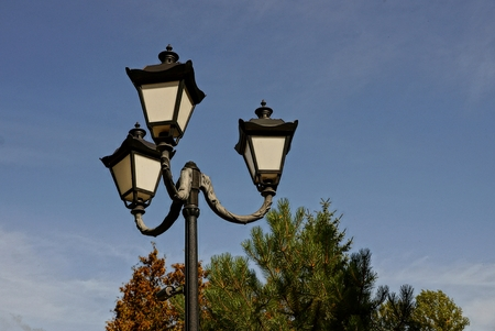 Three ancient street lamp in the park on the sky background Stock Photo