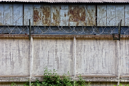 barbed wire fence: barbed wire on a gray concrete fence and rusty building wall