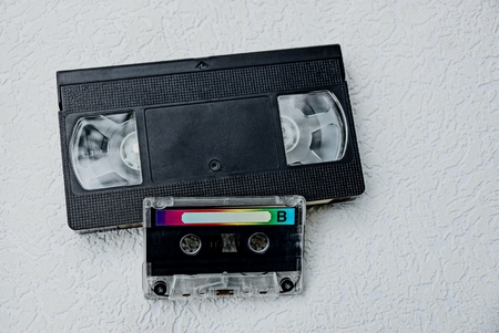 videocassette: cassette audio and black video cassette on a gray table