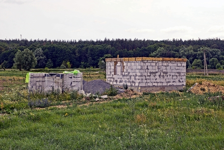 Construction site with unfinished house of white brick on the field in the grass