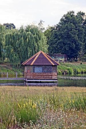 Mooi houten huisje op het meer bij de groene weide
