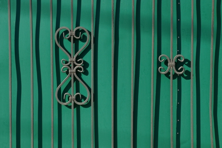 fragment of a green fence with forged rods and a beautiful pattern