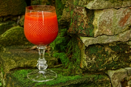 a glass with a red drink stands on bricks covered with moss