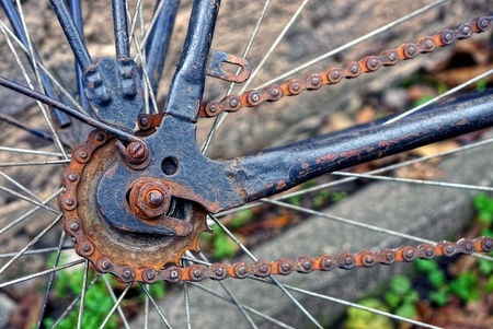 part of an old bicycle with a frame and a rusty chain