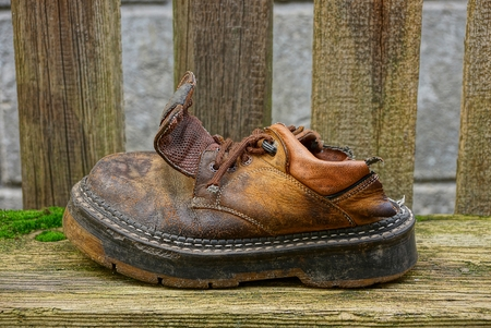 Old ragged brown shoe on a gray board