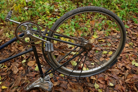 inverted old bicycle with a wheel on dry grass in the open air