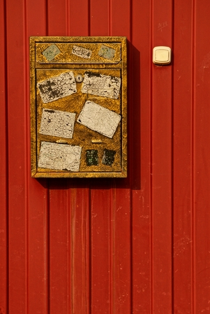 old brown mailbox on an iron red wall Stock Photo