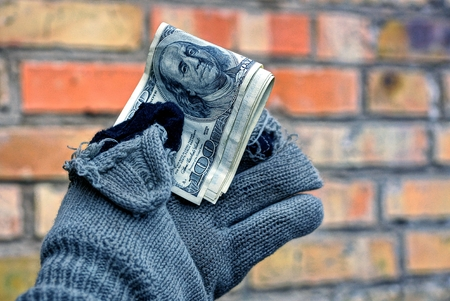 homeless man holding money in a torn glove against a brick wall background