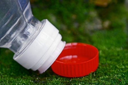 An open plastic bottle and a red cork on a green moss