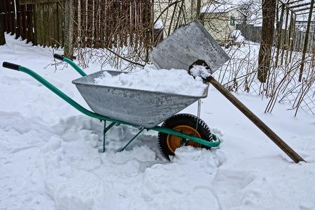 an iron wheelbarrow with snow and a shovel in a snowdrift