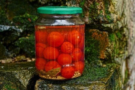 glass jar with canned tomatoes on bricks in green moss Stock Photo