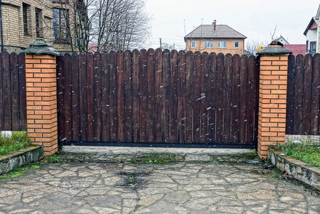 brown wooden closed gate in the street in a blizzard with snow