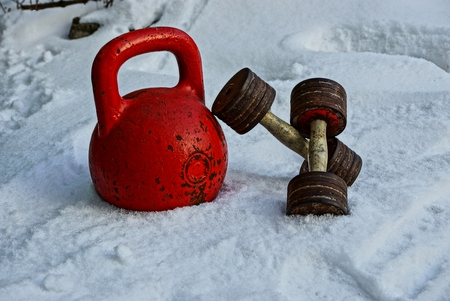 old weights and dumbbells in the street in the snow