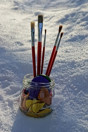 Glass jar with red tassels on snow