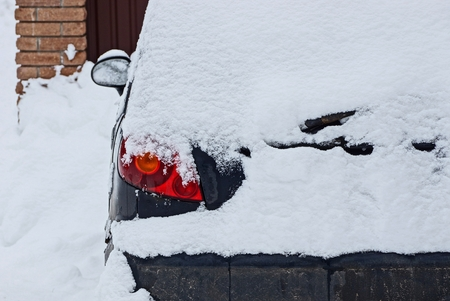 part of a blue car with a headlight under white snow
