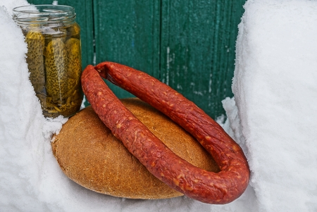 bread sausage and canned cucumbers lie in the snow near the wooden wall