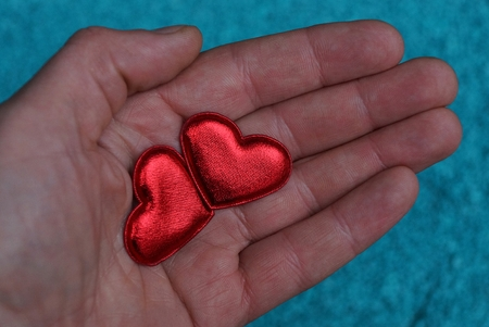 two red hearts lie an an open palm
