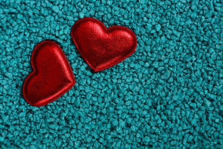 two small red hearts lie on a shallow blue gravel Stok Fotoğraf