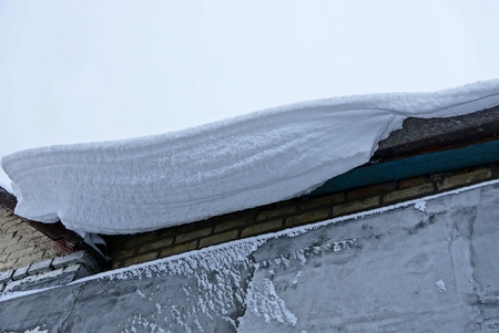 white snow drift on the roof of the house Stock Photo