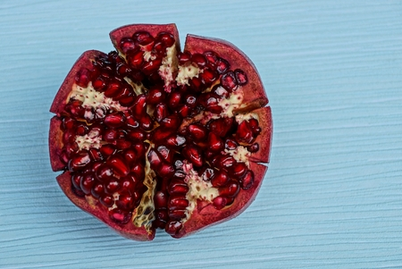 piece of ripe red pomegranate on a blue table Stock Photo