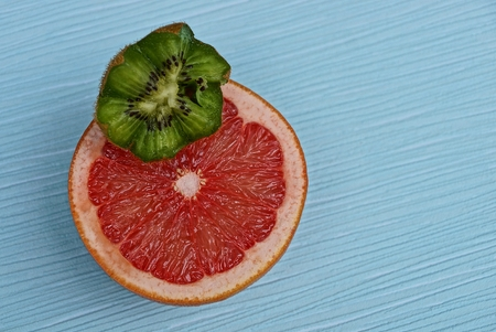 red orange and a piece of green kiwi on a blue table