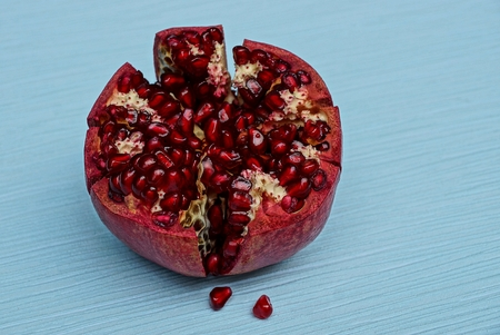 piece of ripe red pomegranate on a blue background