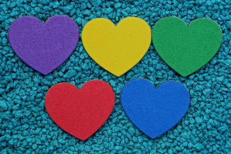 a row of colored hearts on blue small stones