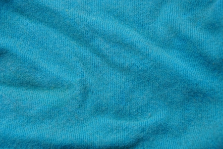 turquoise woolen texture of crumpled old clothes
