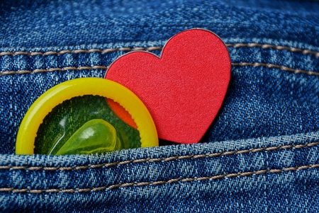 yellow condom and red heart in blue coton pants pocket Stock Photo