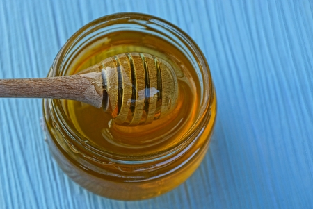 wooden brown spoon in a glass jar of honey on a blue table Stok Fotoğraf