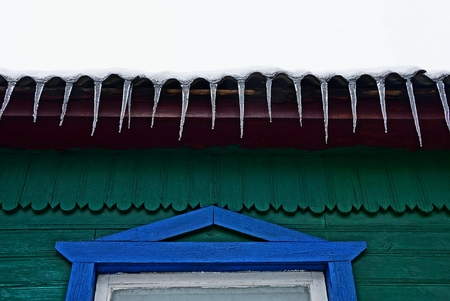 row of icicles on the roof of a wooden house