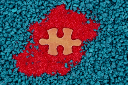 orange puzzle on red sand and blue stones