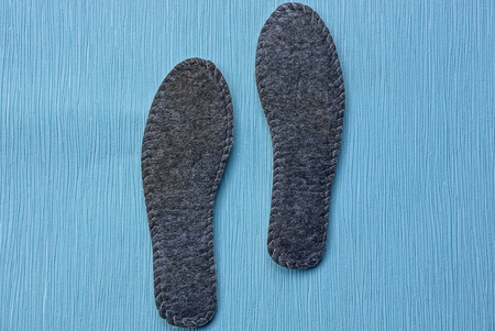 two-dimensional insoles made of felt on a blue table