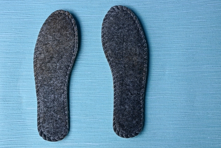 two gray insoles for shoes on blue background Stockfoto